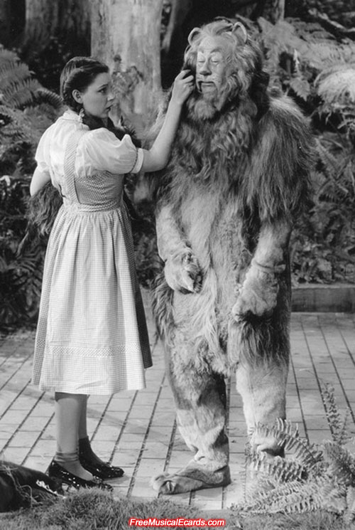 Judy Garland as Dorothy keeps a straight face while wiping away the Cowardly Lions tears