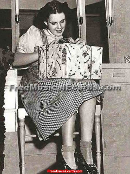 Judy Garland opens a present in her checkered dress and ruby slippers