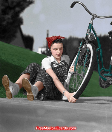 Judy Garland putting a tyre on her bike (Color)
