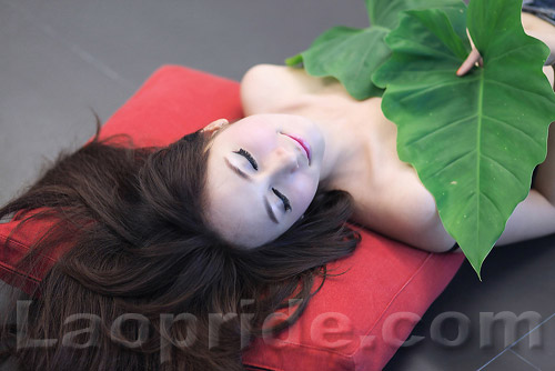 Lao girl covers her breasts with taro leaves