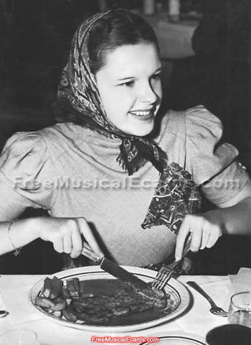 A smiling Judy Garland eating beef steak and potatoes