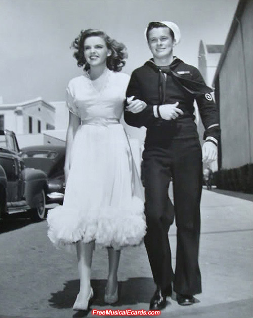 Bombshell singer-actress Judy Garland is escorted by an American sailor