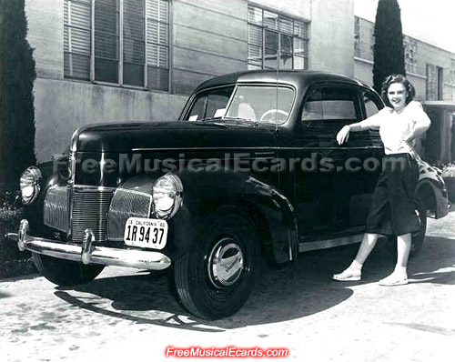 Judy Garland posing with her new 1940 Studebaker Champion Coupe