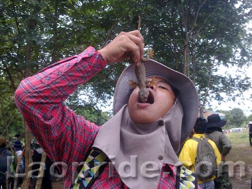 Lao boy eating a lizard