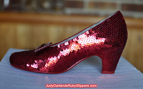 Sequining work is finished with one shoe on Judy Garland's ruby slippers