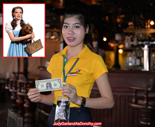 Beerlao girl holds Judy Garland as Dorothy's one dollar bill