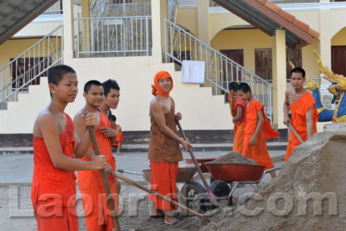 Buddhist monks are hard at work at the temple in Vientiane, Laos