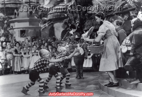 Judy Garland as Dorothy receives a lollipop from the Lollipop Guild