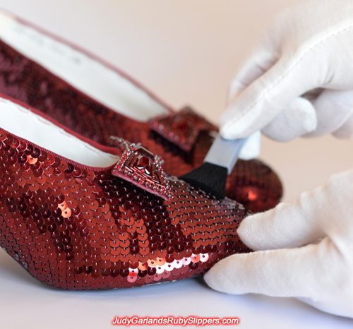 Wiping away dust particles on Judy Garland's ruby slippers