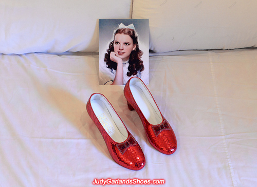 Judy Garland's hand-sewn ruby slippers on a bed
